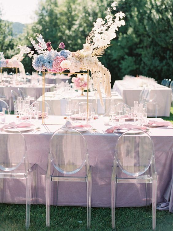 iridescent wedding tablescape with a lilac tablecloth, pink napkins, an eye-catchy iridescent floral arrangement over the table