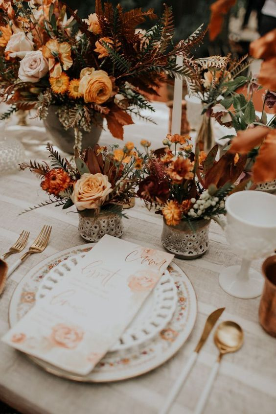 lovely and bright fall boho wedding centerpiece of blush, rust and orange blooms, greenery and colored foliage is amazing