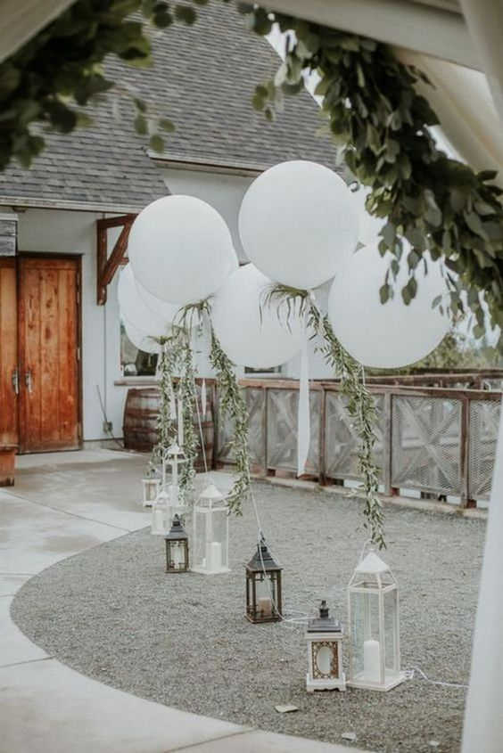 lovely and simple wedding outdoor decor with candle lanterns and white balloons and greenery is a chic and stylish idea