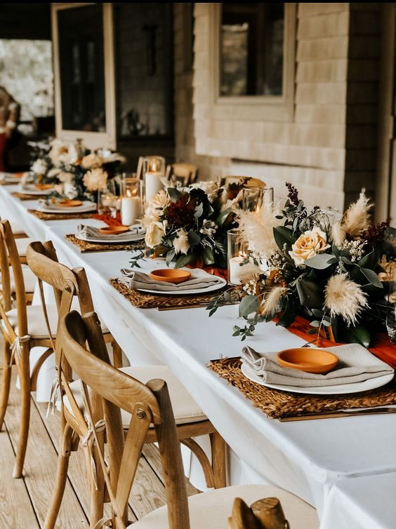 lovely boho fall wedding centerpieces made of various types of greenery, neutral blooms, pampas grass, bold burgundy blooms and foliage
