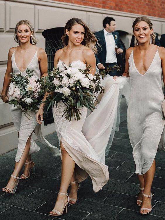 minimalist yet sparkly white midi bridesmaid dresses with deep necklines and side slits are idea for a spring or summer wedding