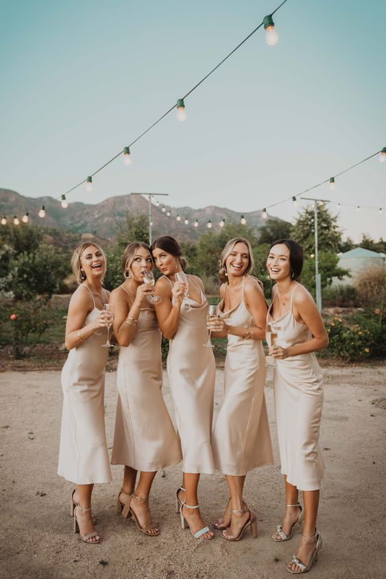 neutral silk slip midi bridesmaid dresses are chic, simple and will never go out of style and a white bridal party is on trend