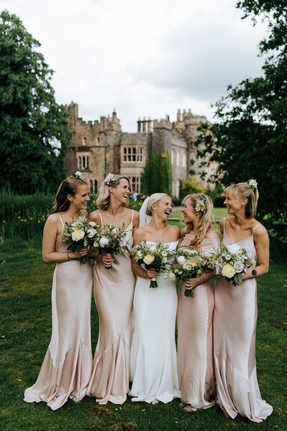 pale pink slip maxi bridesmaid dresses with mermaid tails and V-necklines are amazing for a dreamy castle wedding