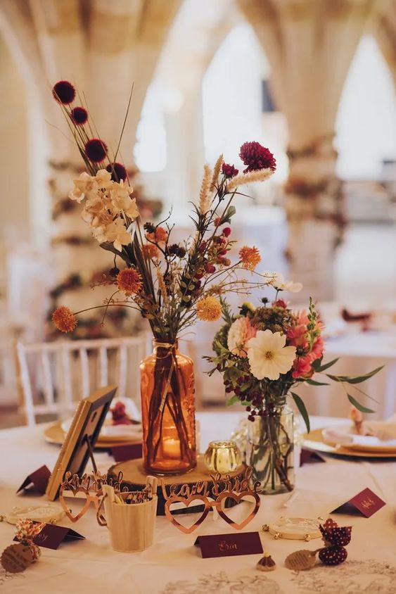 pretty and bright fall boho wedding centerpiece of white, pink, red, rust dried blooms, greenery, a wood slice and candleholders