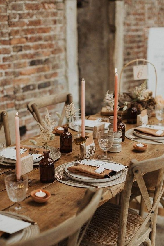 pretty and simple dried flower and bunny tail centerpieces in apothecary bottles, blush and orange candles in tall candleholders