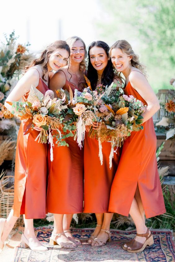 pretty burnt orange midi slip bridesmaid dresses with side slits paired with simple and platform sandals are chic for a boho wedding