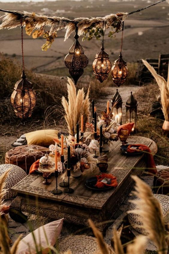 pretty fall boho wedding centerpiece of pampas grass, king proteas, wheat and dried blooms, black and orange candles is gorgeous