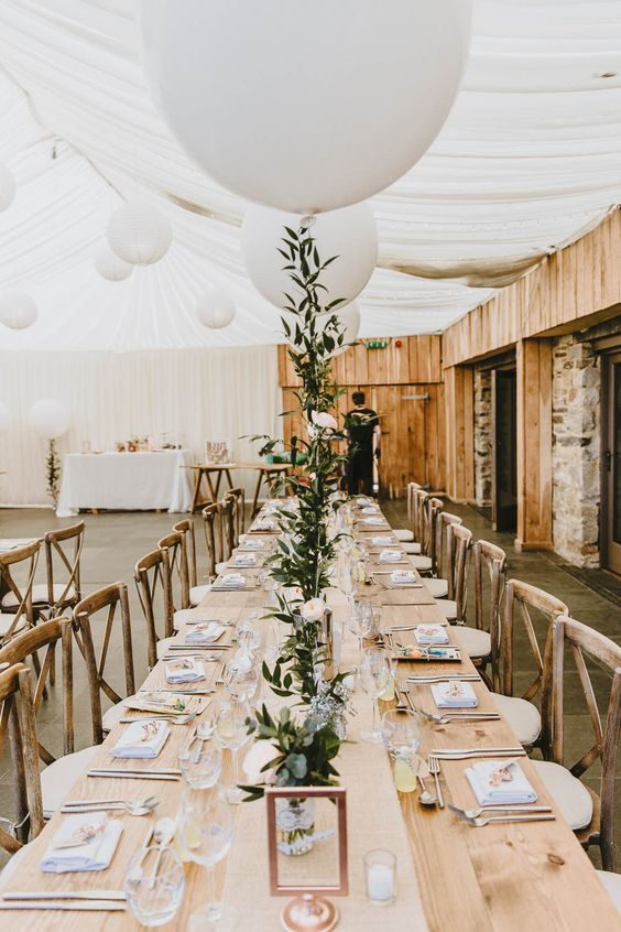 pretty wedding reception tables styled with greenery, white blooms and white balloons plus copper frames is very cool