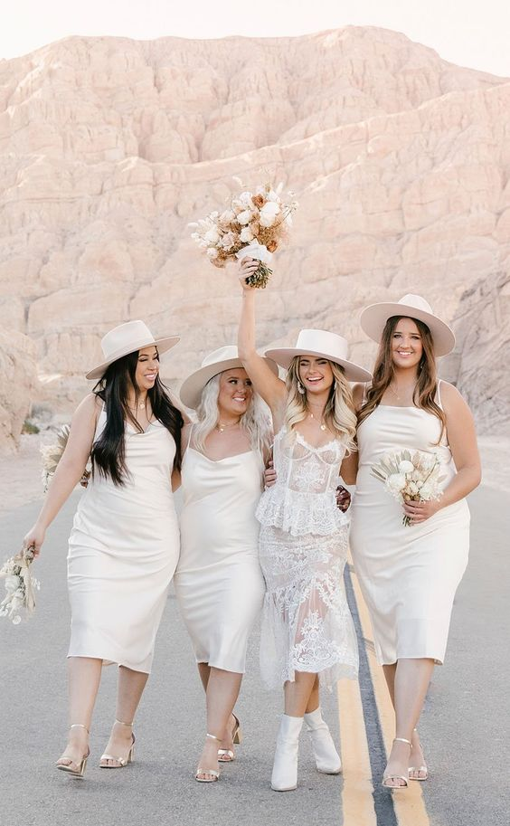 white slip midi bridesmaid dresses, silver heels and hats are amazing for a boho spring or summer bridal party
