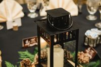 02 a beautiful winter wedding centerpiece of ferns, pinecones, a candle lantern placed on a wood slice and more candles around is a cozy idea
