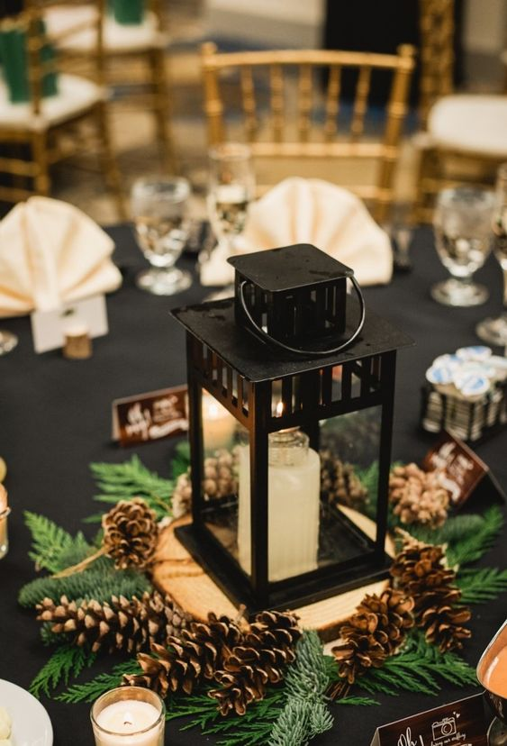 a beautiful winter wedding centerpiece of ferns, pinecones, a candle lantern placed on a wood slice and more candles around is a cozy idea