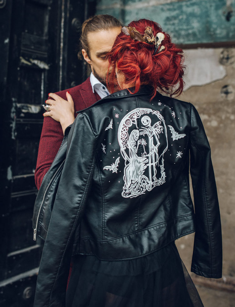 a bride wearing a black wedding dress and a black leather jacket with Tim Burton movie characters painted to personalize it
