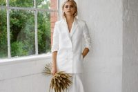 02 a chic and minimalist bridal look with an oversized white blazer and a maxi pleated skirt plus a grass wedding bouquet and statement earrings