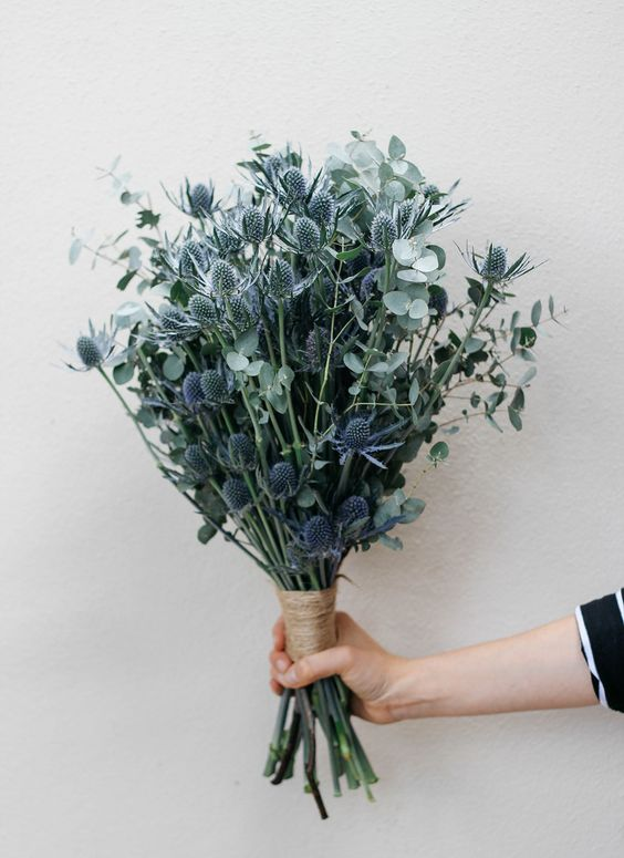 a fabulous wedding bouquet of eucalyptus and blue thistles is a stylish idea for a non-floral minimalist wedding