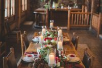 03 a bold cabin winter wedding centerpiece of large pinecones, white and red blooms and evergreens plus pillar candles is amazing