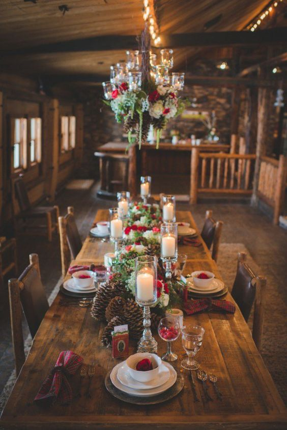 a bold cabin winter wedding centerpiece of large pinecones, white and red blooms and evergreens plus pillar candles is amazing