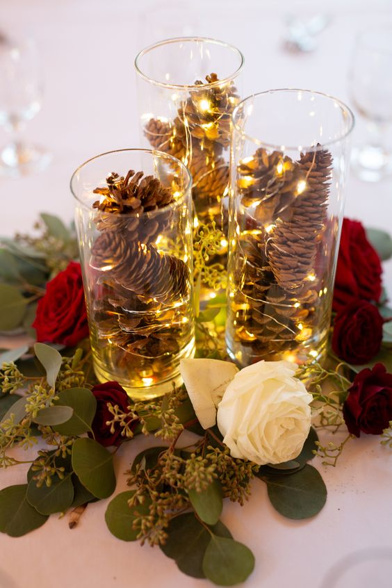 a bold Christmas wedding centerpiece of tall vases with pinecones and LEDs, white and red roses, greenery is a lovely idea to go for