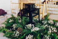 05 a classy winter wedding centerpiece of evergreens, baby's breath, pinecones and a candle lantern in the center is amazing