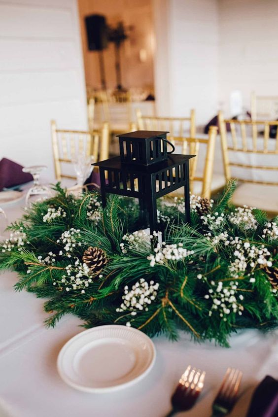 a classy winter wedding centerpiece of evergreens, baby's breath, pinecones and a candle lantern in the center is amazing