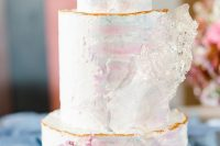 05 a delicate iridescent wedding cake with a gold edge, with pastel pink and blue blooms and some sugar shards is amazing