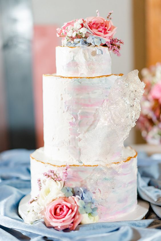 a delicate iridescent wedding cake with a gold edge, with pastel pink and blue blooms and some sugar shards is amazing