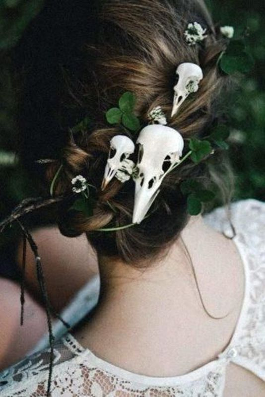 a low wedding updo accented with greenery and bird skulls is a great idea for a Gothic, Halloween or Tim Burton wedding