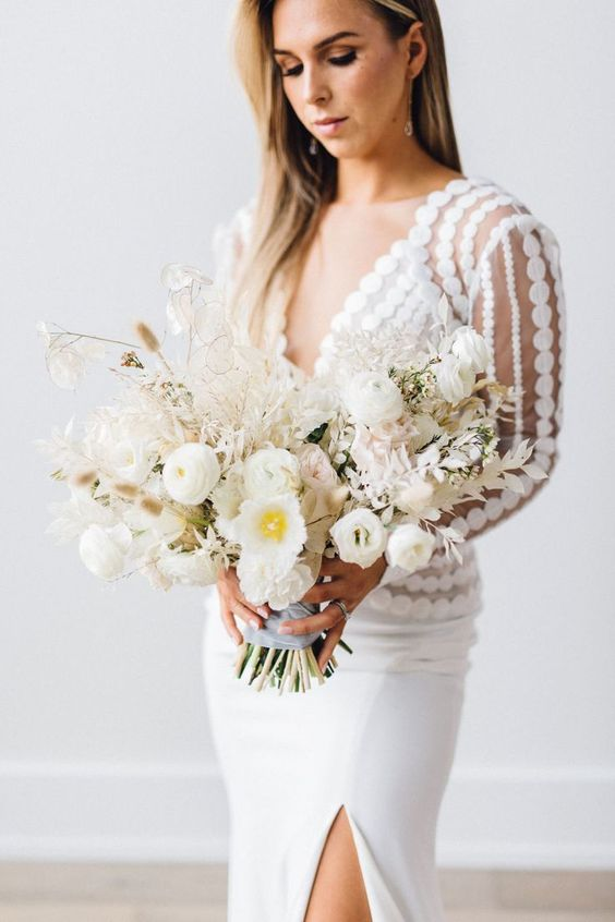 a stylish minimalist bridal look with a polka dot top and a plain pencil skirt plus a lush white flower wedding bouquet
