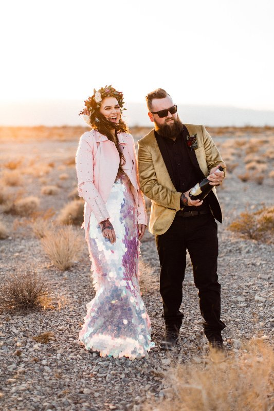 a daring bride wearing a fully iridescent wedding dress and an embellished pink leather jacket plus a floral crown