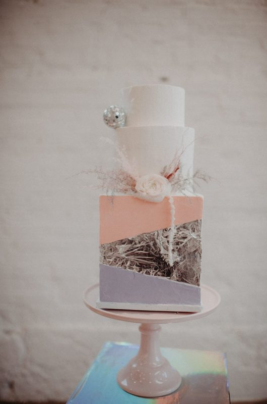 a fantastic iridescent wedding cake with a color block square and tound tiers, a neutral bloom and a disco ball is amazing