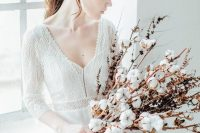 06 a winter bride in a boho lace and plain wedding dress and a cotton bud wedding bouquet for a cozy and warm feel