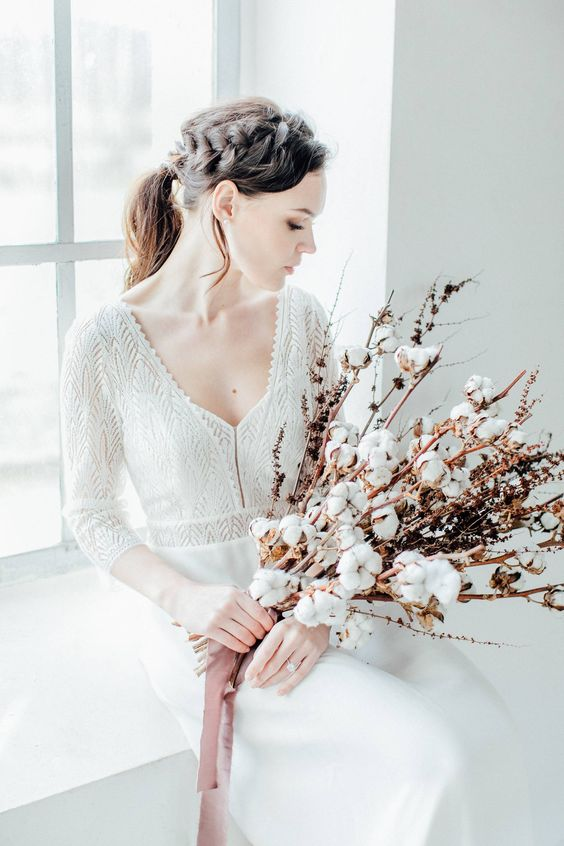 a winter bride in a boho lace and plain wedding dress and a cotton bud wedding bouquet for a cozy and warm feel