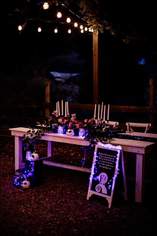 a beautiful Tim Burton wedding reception with pink and dark blooms, greenery, purple lights, candles and artworks is wow