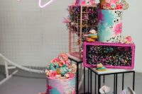 07 a fantastic iridescent wedding sweets station with colorful cakes topped with donuts and cons, with pastel metal boxes and iridescent blooms