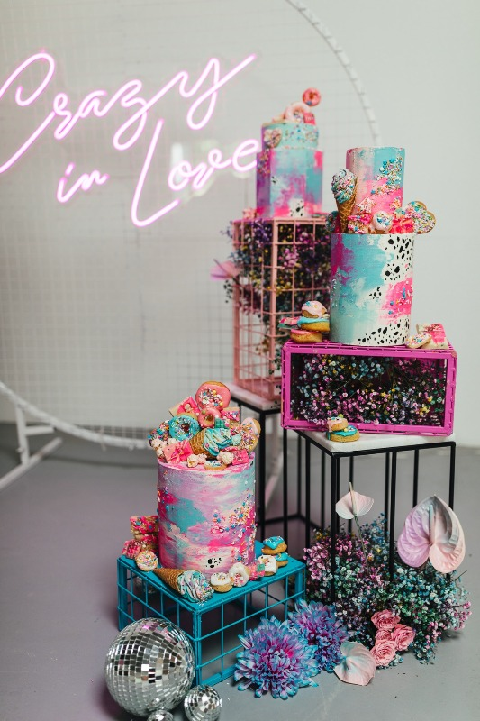 a fantastic iridescent wedding sweets station with colorful cakes topped with donuts and cons, with pastel metal boxes and iridescent blooms