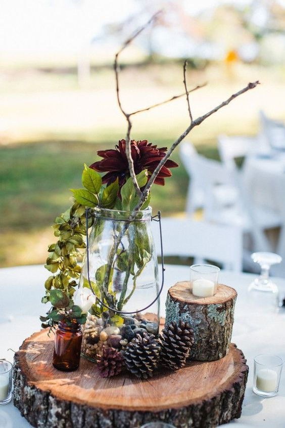 a creative fall woodland wedding centerpiece of a wood slice, pinecones and a small tree stump, a bright statement bloom, greenery and branches