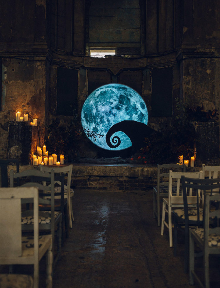 a wedding backdrop inspired by Tim Burton movies looks spooky and chic, with candles around and with blooms on the floor