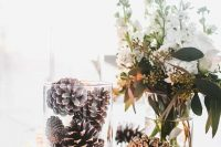 09 a creative winter wedding centerpiece of white blooms and greenery, pinecones in a glass and more on the table, some candles is cool