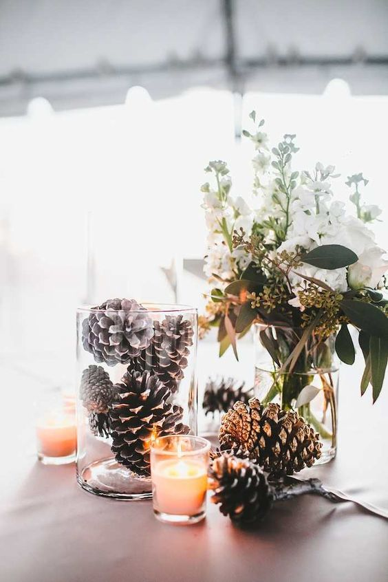 a creative winter wedding centerpiece of white blooms and greenery, pinecones in a glass and more on the table, some candles is cool