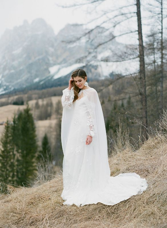 a jaw dropping refined winter bridal look with an off the shoulder petal wedding dress, a sheer capelet and matching earrings