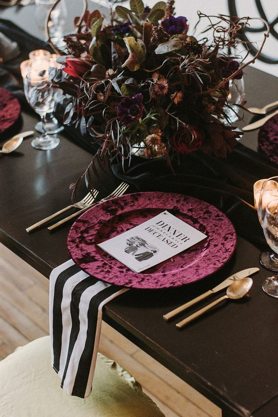a stylish Halloween Tim Burton wedding tablescape with a beautiful moody dark floral centerpiece, burgundy chargers, gold cutlery and striped napkins