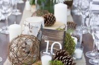 10 a cute winter wedding centerpiece of a wood slice, pinecones, a vine ball, moss, white blooms and pillar candles is a very cozy idea