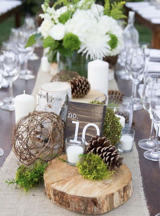 a cute winter wedding centerpiece of a wood slice, pinecones, a vine ball, moss, white blooms and pillar candles is a very cozy idea