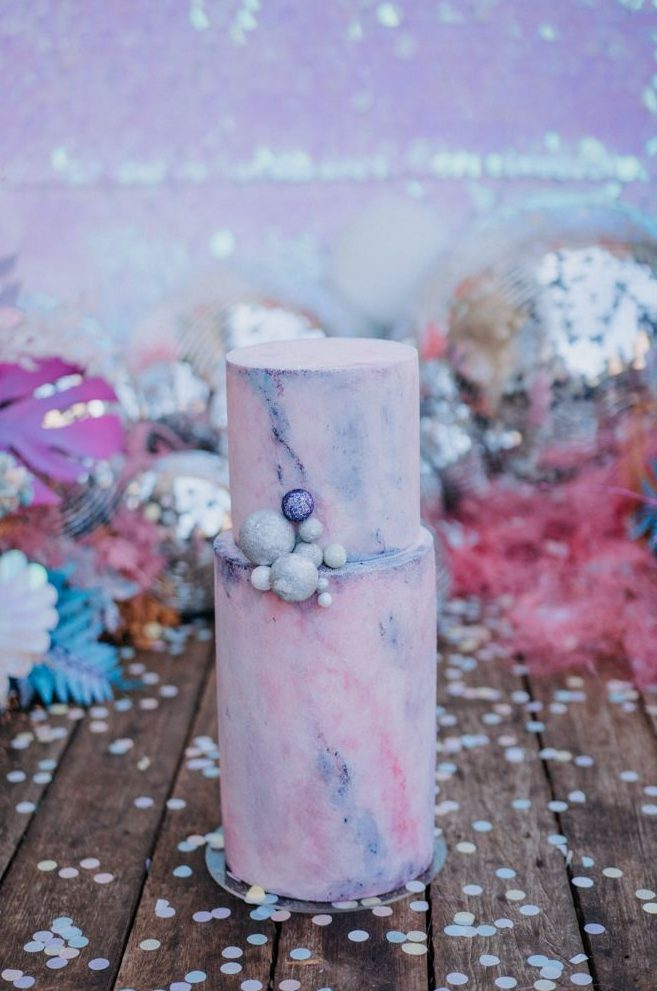 a jaw dropping iridescent wedding cake done with a blue and pink marble effect and some mini disco balls is a gorgeous solution