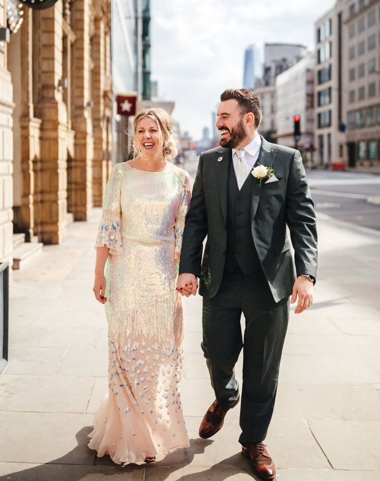 an iridescent wedding dress with a catchy spots on the skirt, with flare sleeves and a high necklace is gorgeous