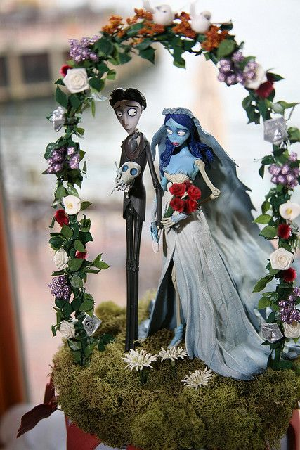 moss and Sally and Jack decor with a floral wedding arch is a stunning idea for a Nightmare Before Christmas wedding