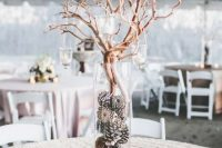 11 a frosty winter wedding centerpiece of a tall vase with pinecones and branches with candleholders plus more candles around