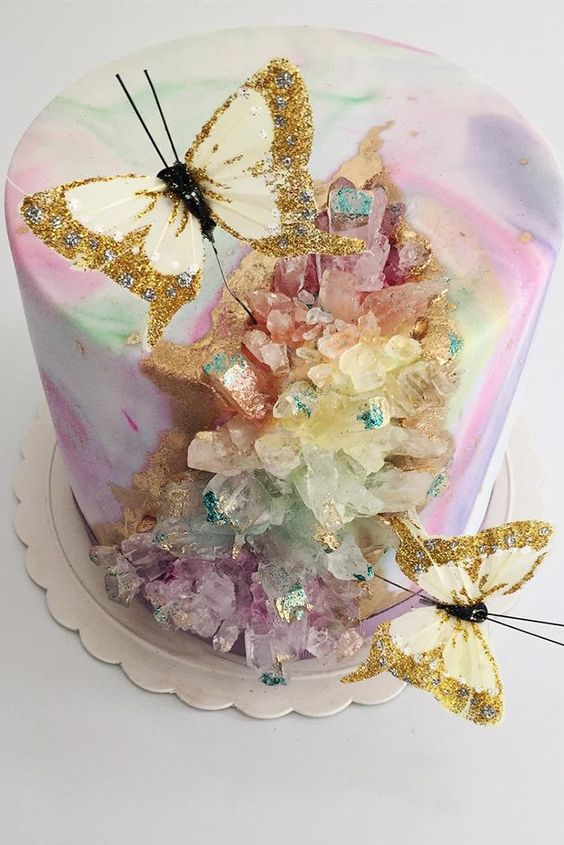 a jaw dropping iridescent wedding cake with iridescent geodes and glitter faux butterflies is a gorgeous solution to try