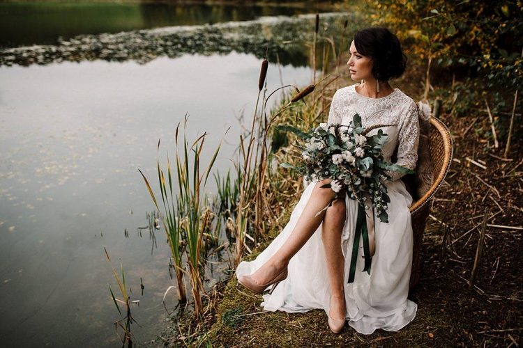 a winter bride in a refined lace A-line wedding dress, statement earrings, nude shoes and a cool neutral and greenery wedding bouquet