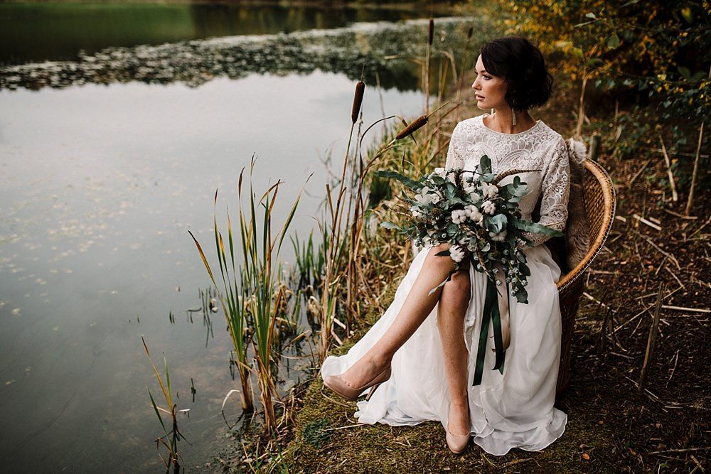 a winter bride in a refined lace A line wedding dress, statement earrings, nude shoes and a cool neutral and greenery wedding bouquet
