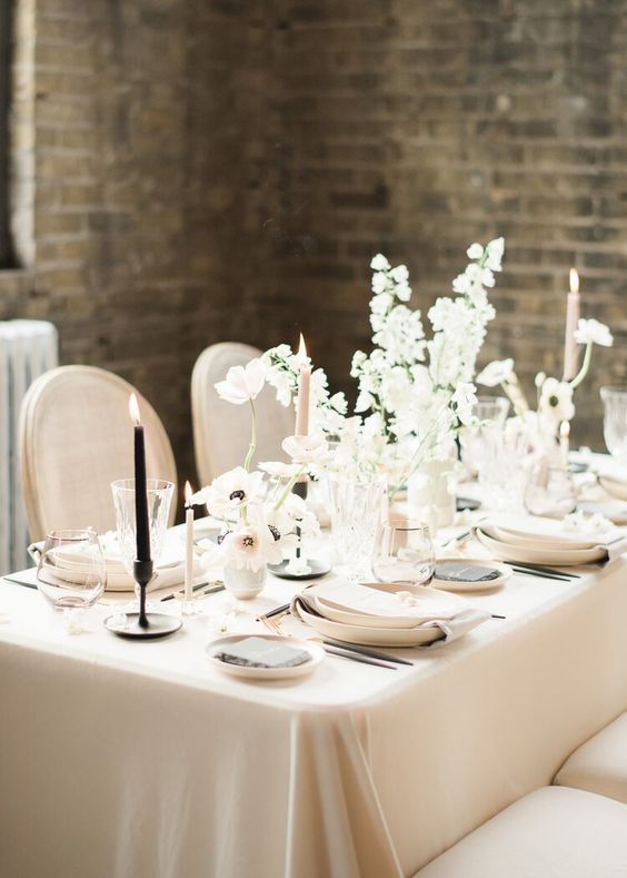 a beautiful and sophisticated neutral winter wedding tablescape with warm colored linens and plates, white blooms, pink and black candles